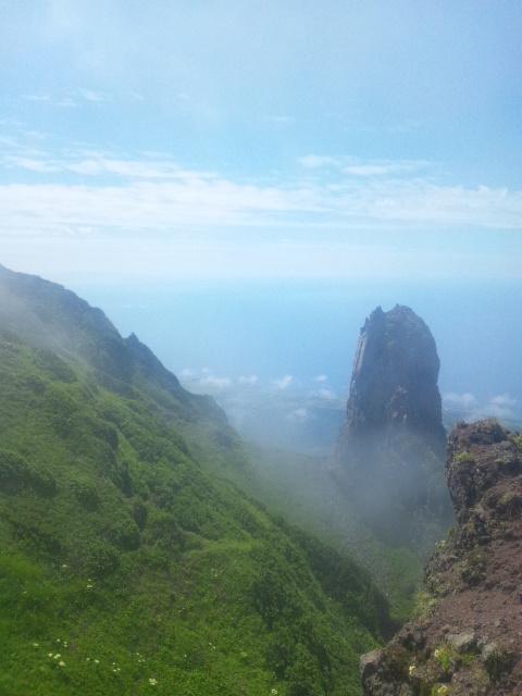 山頂のろうそく岩、その向こうに天売島、焼尻島と留萌の辺りの山並みが見えます